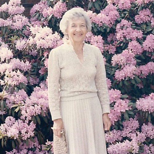 dolly ahrens in front of her purple flowers